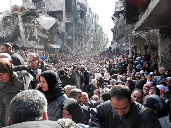 The besieged Palestinian camp of Yarmouk, queuing to receive food supplies, in Damascus, Syria. The Guardian, Feb 26, 2014.